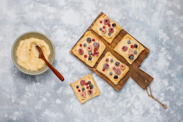 Świeże pyszne ciasto francuskie ze słodkimi jagodami na betonie