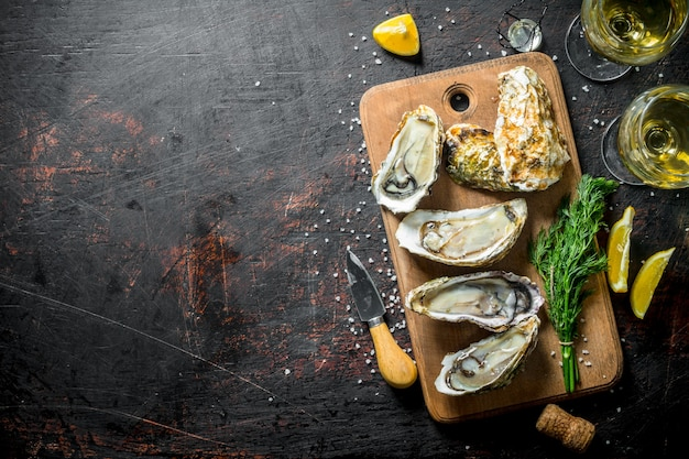 Świeże, pyszne ostrygi z białym winem, cytryną i koperkiem na czarnym rustykalnym stole