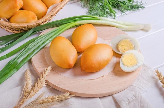Świeże pyszne paszteciki nadziewane gotowanymi jajkami na okrągłej drewnianej desce na białym drewnianym tle