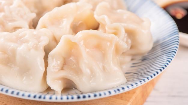 Świeże, pyszne pierożki gyoza gotowane wieprzowe, jiaozi na białym tle z sosem sojowym i pałeczkami, z bliska, styl życia. koncepcja projektu domowej roboty.