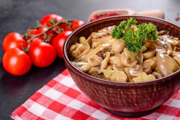 Świeże pyszne pikantne grzyby w puszkach z przyprawami i ziołami w naczyniach ceramicznych na ciemnym tle betonu