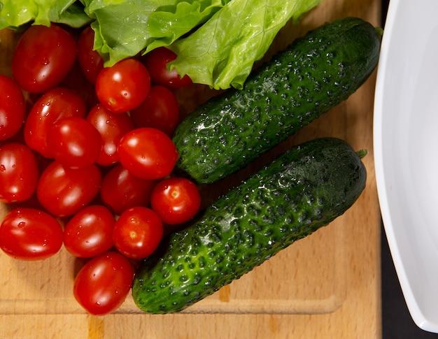 Świeże pyszne warzywa: pomidorki koktajlowe, ogórki korniszony i liście sałaty z kroplami rosy