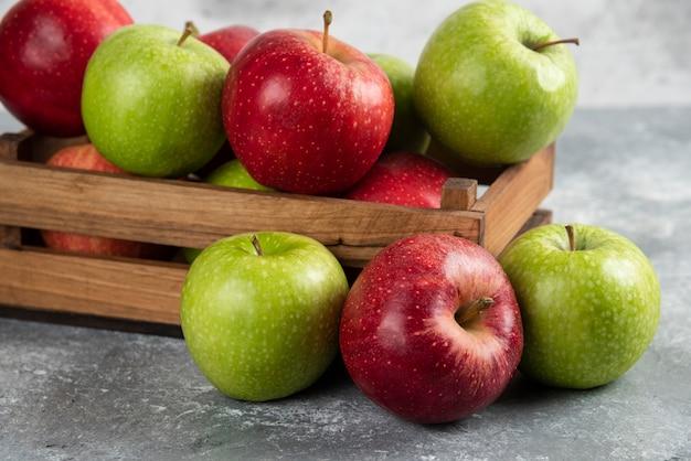 Świeże pyszne zielone i czerwone jabłka w drewnianym pudełku.