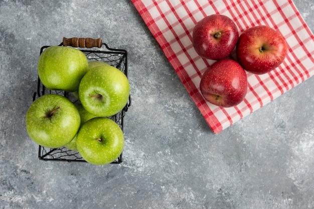 Świeże pyszne zielone i czerwone jabłka w metalowym koszu na marmurowej powierzchni.