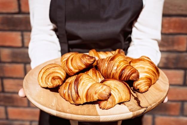 Świeże rogaliki. ciepłe pachnące maślane rogaliki i bułki na drewnianym stojaku w rękach szefa kuchni. ciastka francuskie i amerykańskie.