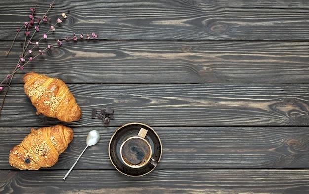 Świeże rogaliki i filiżanka espresso z bukietem wiosennych kwiatów na stole