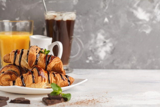 Świeże rogaliki śniadaniowe z syropem czekoladowym, sokiem pomarańczowym i kakao z pianką. skopiuj miejsce koncepcja deser kuchni francuskiej.