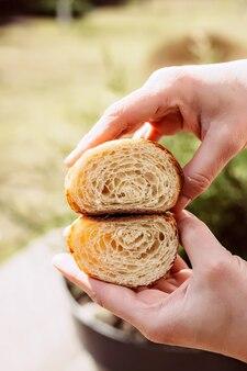 Świeże rogaliki w krojeniu w rękach szefa kuchni. ciepłe aromatyczne rogaliki maślane. ciastka francuskie i amerykańskie.