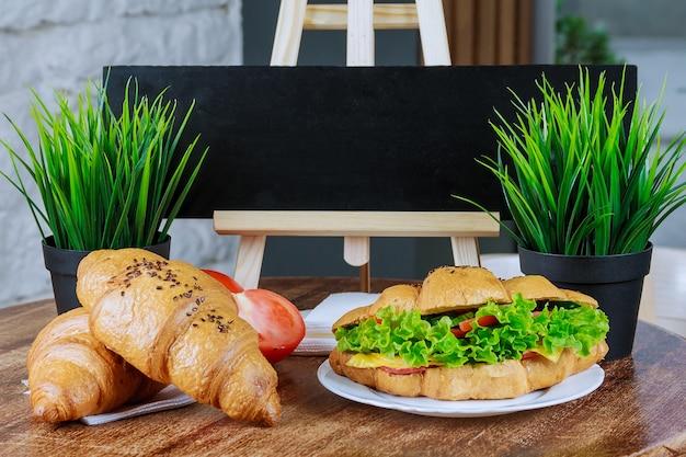 Świeże rogaliki z wieprzowiną kurczak pomidory sałatka ogórki na białym talerzu na drewnianym stole.