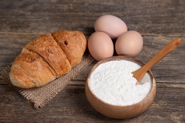Świeże rogaliki zwykłe, mąka i surowe jajka na powierzchni drewnianych. wysokiej jakości zdjęcie