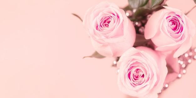 Świeże róże ozdobione są koralikami na delikatnym różu.