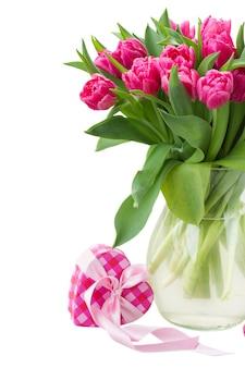 Świeże różowe kwiaty tulipanów w szklanym wazonie na białym tle
