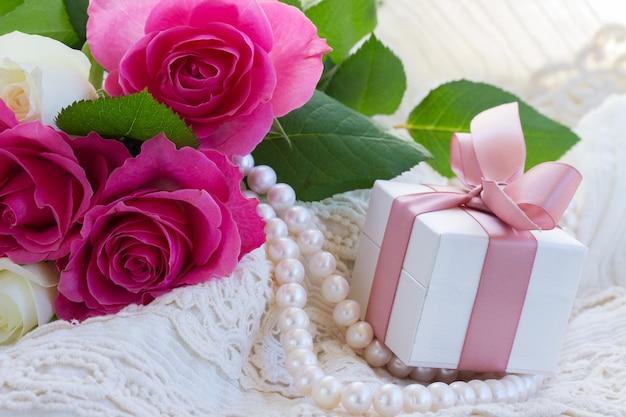 Świeże różowe róże z koronką, perłami i pudełkiem prezentowym