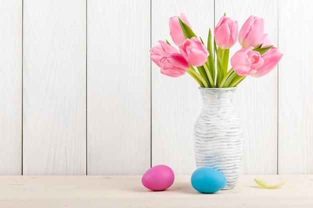 Świeże różowe tulipany i pisanki na drewnie