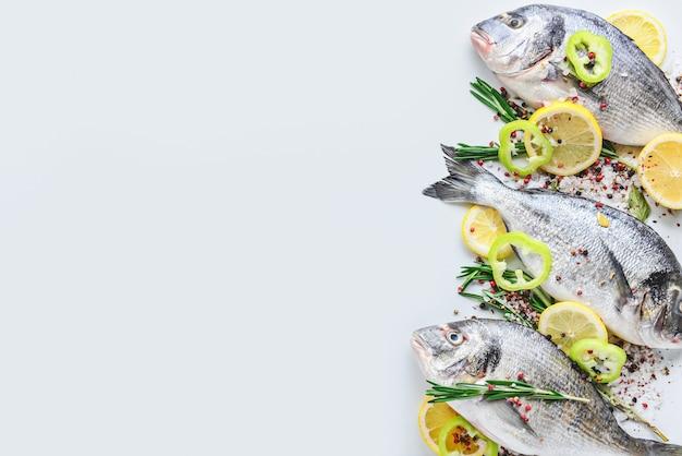Świeże ryby dorado i przyprawy na białym?