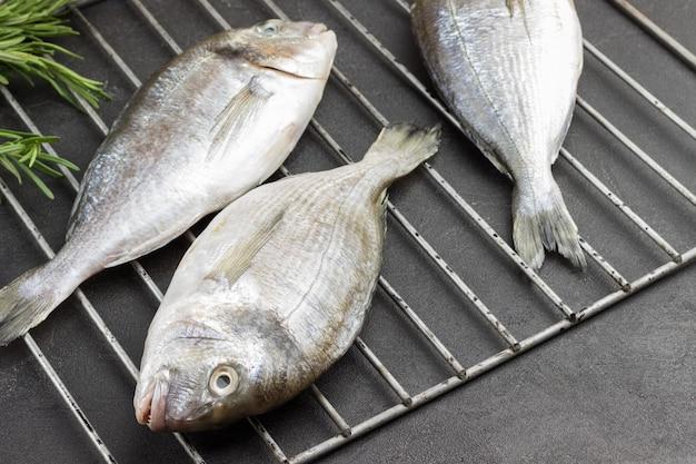 Świeże ryby dorado na metalowym grillu.