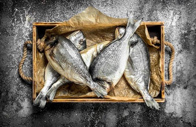 Świeże ryby dorado na starej tacy.