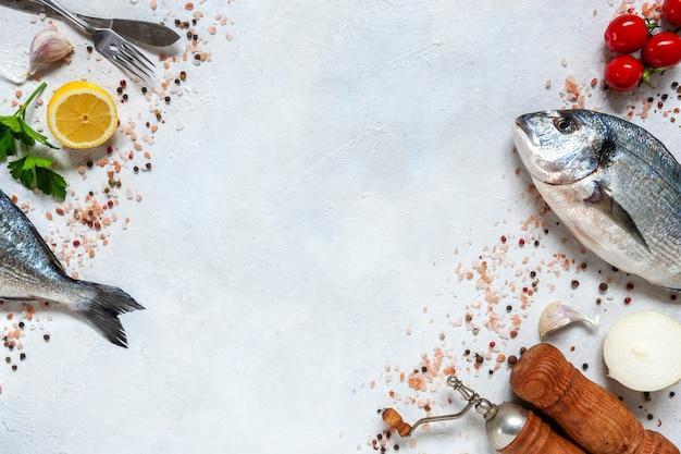Świeże ryby dorado z przyprawami, czosnkiem, białą cebulą i przyprawami na białym naczyniu na białym stole