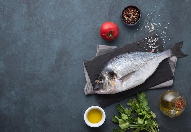 Świeże ryby dorado z przyprawami ziół i oleju na czarnej desce do krojenia