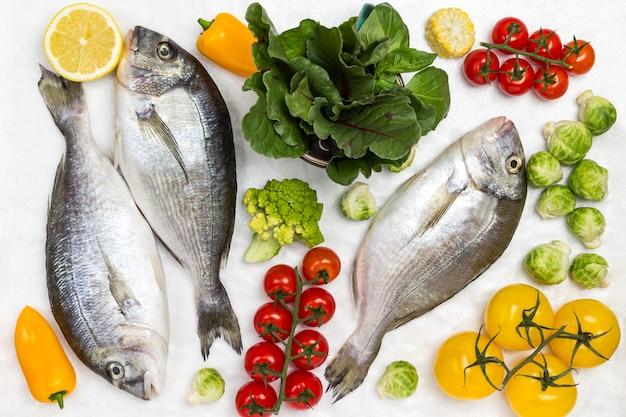 Świeże ryby dorado z warzywami i zielenią.