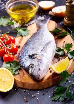 Świeże ryby dorado z warzywami na ciemno