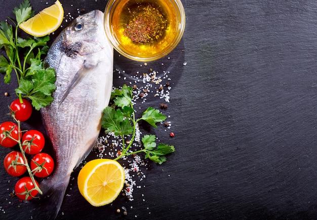 Świeże ryby dorado z warzywami na ciemny, widok z góry