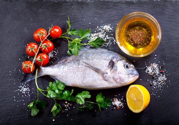 Świeże ryby dorado ze składnikami do gotowania na ciemnym widoku z góry