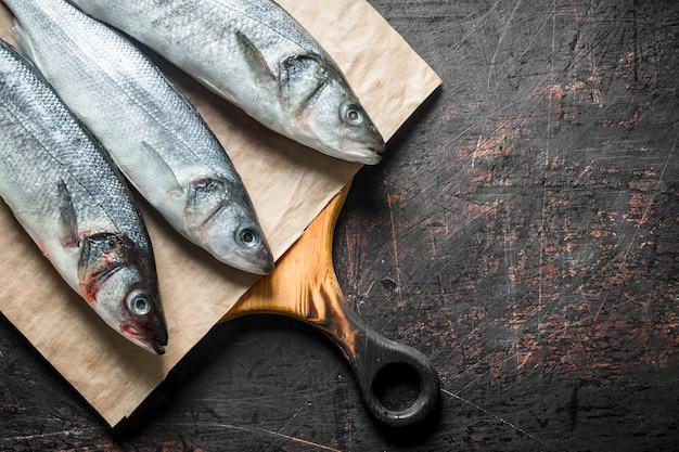 Świeże ryby labraks na papierze. na ciemnym tle rustykalnym
