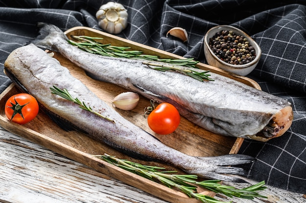 Świeże ryby mintaja. surowe owoce morza. białe tło drewniane. widok z góry.