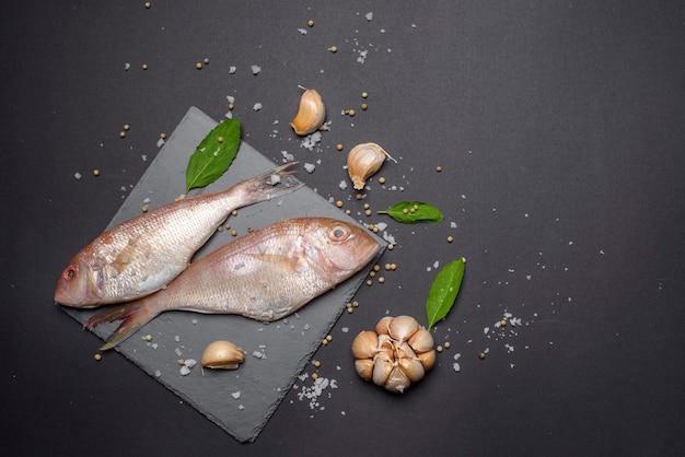 Świeże ryby morskie płasko leżały kopia przestrzeń na czarnym tle