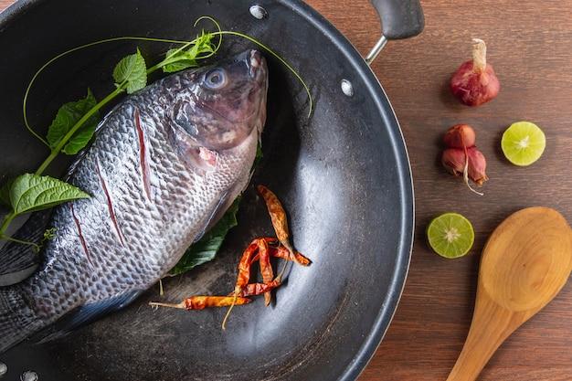 Świeże ryby na patelni i przyprawy do gotowania