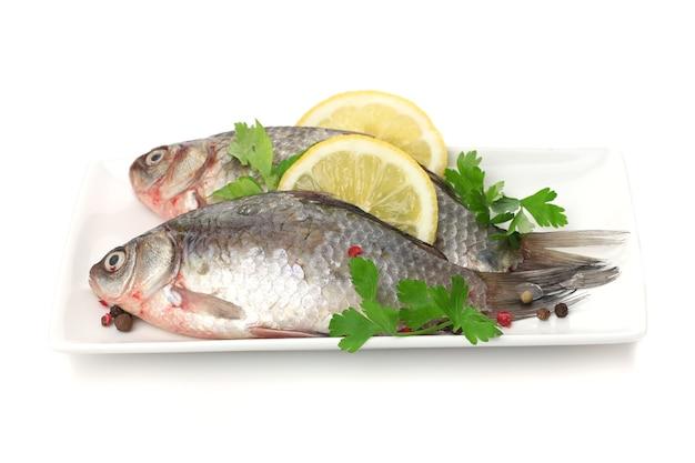 Świeże ryby z cytryną i pietruszką na talerzu na białym tle