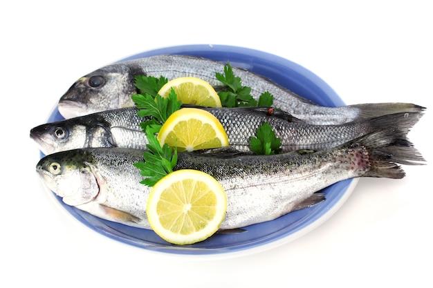 Świeże ryby z cytryną i pietruszką na talerzu na białym?