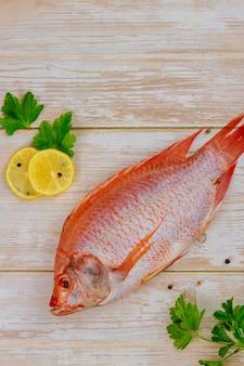 Świeże ryby z ziołami i cytryną na drewnianym stole. widok z góry.