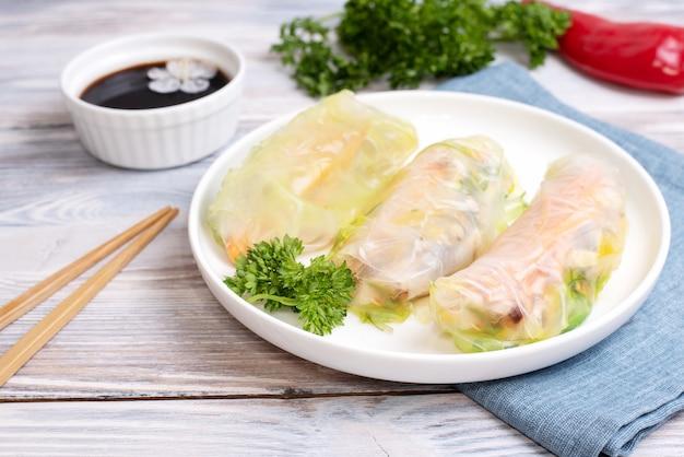 Świeże sajgonki na białym talerzu z tekstyliami i sosem sojowym