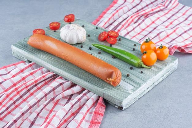 Świeże salami i warzywa na drewnianym talerzu.