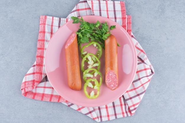 Świeże salami na różowym talerzu z papryką.