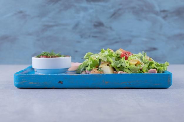 Świeże sałatki i gotowane kiełbaski na niebieskim talerzu.