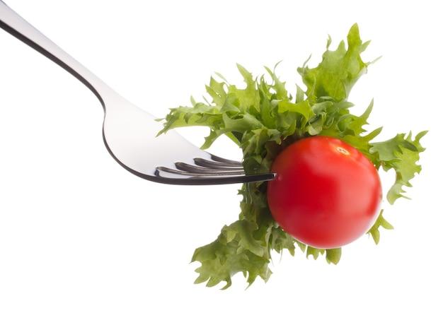 Świeże sałatki i pomidory cherry na widelec na białym tle na białym tle wyłącznik. koncepcja zdrowego odżywiania.