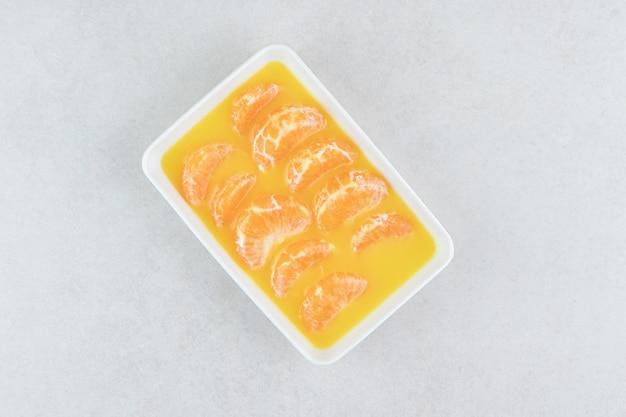 Świeże segmenty mandarynki na białej płytce.