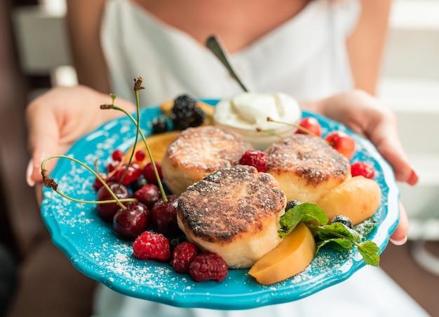 Świeże serniki z jagodami. serniki z jagodami owoców leśnych na niebieskim talerzu.