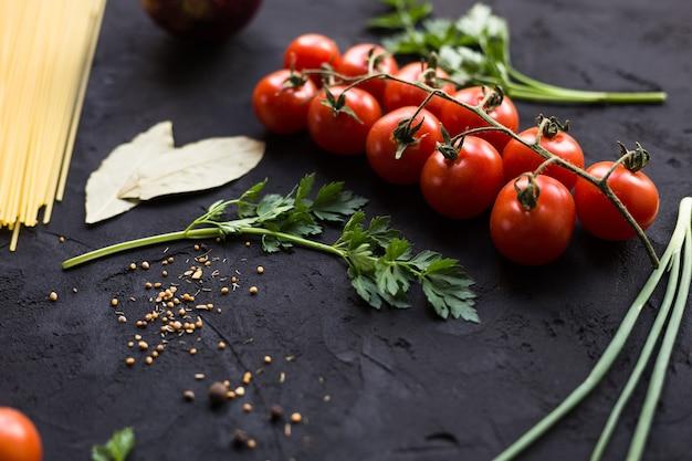 Świeże składniki do gotowania makaronu, pomidorów, cebuli, czosnku, ziół, grzybów i przypraw na czarnym stole z miejscem na kopię