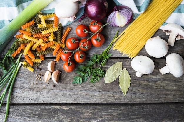 Świeże składniki do gotowania makaronu, pomidorów i przypraw na drewnianym stole z miejsca na kopię