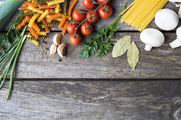 Świeże składniki do gotowania makaronu, pomidorów i przypraw na tle drewniany stół z miejsca na kopię