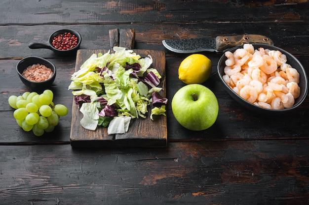 Świeże składniki do smacznego zestawu sałatek z krewetkami waldorf, z sosem jabłkowym i winogronowym, na starym ciemnym drewnianym stole, z miejscem na kopię na tekst