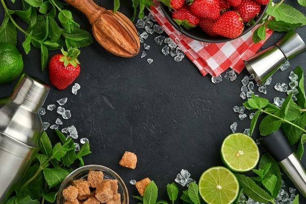 Świeże składniki spożywcze do przygotowania lemoniady, naparowanej wody detoksykującej lub koktajlu. truskawki, limonka, mięta, bazylia, cukier trzcinowy, kostki lodu i shaker na czarnym tle kamiennym lub betonowym. widok z góry.