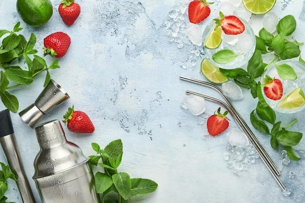 Świeże składniki spożywcze do przygotowania lemoniady, naparowanej wody detoksykującej lub koktajlu. truskawki, limonka, mięta, bazylia, kostki lodu i shaker na niebieskim lub szarym kamieniu lub betonowym tle widok z góry z miejscem na kopię