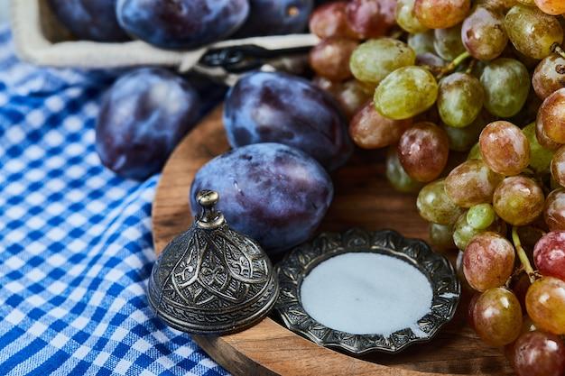 Świeże śliwki i kiść winogron na drewnianym talerzu.