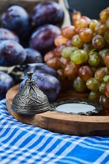 Świeże śliwki i kiść winogron na obrusie.