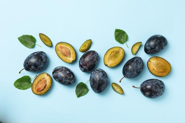 Świeże śliwki i liście na niebiesko, widok z góry